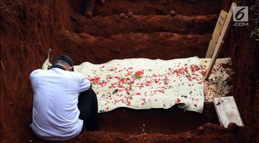 Seorang keluarga korban di liang lahat saat penguburan massal korban kecelakaan bus Tanjakan Emen Subang di TPU Legoso Ciputat, Tangerang Selatan, Banten, Minggu (11/2). Prosesi dihadiri oleh keluarga, kerabat, serta masyarakat. (Liputan6.com/JohanTallo)
