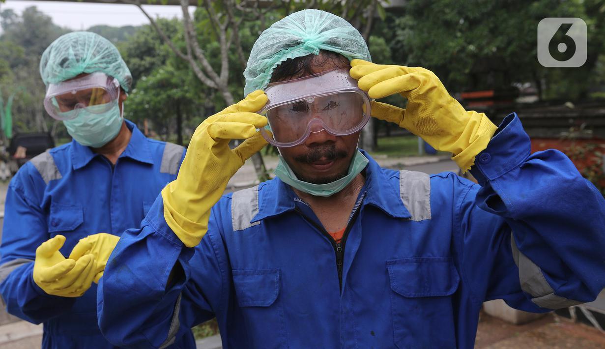 Petugas memasang kacamata dan masker sebelum menyemprotkan cairan disinfektan di area Museum Fauna Indonesia Komodo dan Taman Reptilia, TMII Jakarta, Rabu (18/3/2020). Pengelola TMII secara bertahap melakukan tindakan disinfeksi di setiap lokasi wisata dan anjungan. (Liputan6.com/Fery Pradolo)