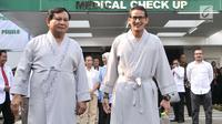 Bakal calon presiden dan wakil presiden Pilpres 2019, Prabowo Subianto (kiri) dan Sandiaga Uno menyapa awak media saat akan menjalanai pemeriksaan awal tes kesehatan di RSPAD Gatot Soebroto, Jakarta, Senin (13/8). (Merdeka.com/Iqbal S. Nugroho)