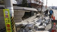Pria membantu membersihkan puing-puing setelah dinding rumah runtuh di kota Kunimi, utara kota Fukushima, timur laut Jepang, Minggu (14/2/2021).  Gempa bumi berkekuatan 7,1 magnitudo mengguncang prefektur Fukushima, Jepang, pada Sabtu (13/2/2021) malam. (Jun HIrata/Kyodo News via AP)