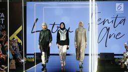 Fenita Arie (tengah) bersama para model berjalan di atas catwalk mengenakan busana L.tru X Fenita Arie dalam ajang Jakarta Moderat Fashion Week, di Gandaria City, Jakarta, Jumat, (27/7). (Kapanlagi.com/Agus Apriyanto)
