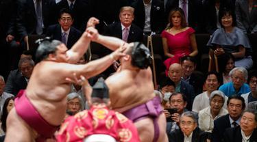 Presiden AS Donald Trump (dua kiri) didampingi PM Jepang Shinzo Abe (kiri) menyaksikan Tokyo Grand Sumo Tournament di Stadion Ryogoku Kokugikan, Tokyo, Jepang, Minggu (26/5/2019). Nonton bareng ini dilakukan di sela-sela kunjungan kenegaraan Trump ke Jepang. (AP Photo/Evan Vucci)