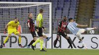 Striker Lazio, Joaquin Correa (kanan) melepaskan tendangan yang berbuah gol pertama timnya ke gawang AC Milan dalam laga lanjutan Liga Italia 2020/2021 pekan ke-33 di Olimpico Stadium, Roma, Senin (26/4/2021). Lazio menang 3-0 atas AC Milan. (AP/Gregorio Borgia)