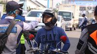 Cek Suhu Tubuh Saat PSBB Tangsel: Petugas memeriksa suhu tubuh pengendara saat pelaksanaan PSBB di kawasan Gading Serpong, Tangerang Selatan, Sabtu (18/4/2020). Pengukuran suhu tubuh tersebut merupakan cek point dari PSBB yang baru saja diberlakukan di Tangerang Raya. (Liputan6.com/Angga Yuniar)