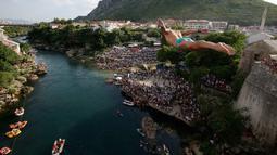Peserta melompat dari Jembatan Old Mostar pada kompetisi menyelam tradisional ke-452 di Mostar, Bosnia, 29 Juli 2018. Penyelam berlari sebelum melompat dari jembatan, jatuh ke sungai dan terbang di udara seperti burung melakukan trik. (AP/Amel Emric)