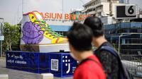 Pejalan kaki melintas di depan Tugu Sepatu, Sudirman, Jakarta, Minggu (19/9/2021). Tugu Sepatu menjadi sasaran pencoretan dengan semprotan aerosol oleh orang tak dikenal sehari usai diresmikan pada 17 September 2021. (Liputan6.com/Faizal Fanani)