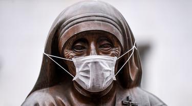 Masker terpasang pada wajah patung Bunda Teresa di Pristina, Kosovo, Kamis (19/12/2019). Pristina dan beberapa kota di Kosovo mengalami polusi udara tingkat tinggi. (Armend NIMANI/AFP)