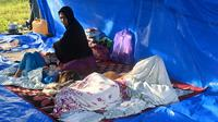 Sebuah keluarga beristirahat di tenda setelah gempa berkekuatan 6,2 di Mamuju, Senin (18/1/2021). Sebanyak 27.850 jiwa telah mengungsi di sejumlah posko pengungsian karena rumah mereka rusak akibat gempa. (AFP/Adek Berry)