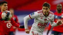 Bek Brest, Romain Perraud (kanan) mengontrol bola di depan pemain Lille dalam laga lanjutan Liga Prancis 2020/21 pekan ke-25 di The Stade Pierre Mauroy, Lille, Minggu (14/2/2021). Brest bermain imbang 0-0 dengan Lille. (AP/Michel Spingler)