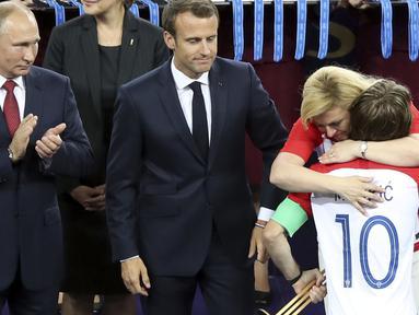 Pelukan hangat Presiden Kroasia, Kolinda Grabar-Kitarovic untuk Luka Modric usai final Piala Dunia 2018 di Luzhniki Stadium, Moskow, Rusia, (15/7/2018). Meski Kroasia kalah Kolinda tetap tersenyum manis. (AP/Thanassis Stavrakis)