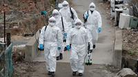Tentara Korea Selatan yang mengenakan pakaian pelindung berjalan untuk menyemprotkan desinfektan di Seoul, Selasa (3/3/2020). Seoul mengerahkan tentara untuk menyemprotkan disinfektan di jalan dan gang-gang untuk mencegah penyebaran virus corona COVID-19. (AP Photo/Lee Jin-man)