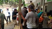 Petugas kepolisian dibantu warga mengevakuasi jasad Maxi yang diduga meninggal dunia akibat keracunan Kuah Bugis. (Liputan6.com/ Arfandi Ibrahim)