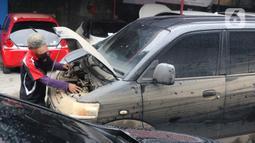 Mekanik mengecek mesin mobil yang terendam banjir di sebuah bengkel di Jakarta, Rabu (8/1/2020). Kerusakan pada mobil yang terendam banjir meliputi interior, kabel dan kelistrikan, serta bagian mesin. (Liputan6.com/Angga Yuniar)