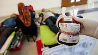 Petugas Palang Merah Indonesia (PMI) menunjukan darah yang sudah dimasukan ke Jakarta, Minggu (3/12). Kegiatan donor darah tersebut diadakan dalam rangkaian acara Natal. (Liputan6.com/JohanTallo)