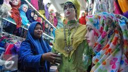 Seorang penjual tampak merapikan barang dagangannya di Pasar Tanah Abang, Jakarta, Kamis (2/7/2015). Memasuki pertengahan Ramadan pedagang mengaku penjualan baju muslim meningkat dari bulan-bulan sebelumnya. (Liputan6.com/Yoppy Renato)