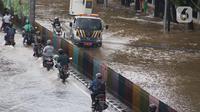 Sejumlah pengendara nekat menerobos genangan banjir di Jalan dr Sutomo, Pasar Baru, Jakarta, Selasa (25/2/2020). Hujan yang mengguyur Jakarta sejak Senin (24/2) malam membuat sejumlah kali meluap dan menyebabkan banjir. (Liputan6.com/Helmi Fithriansyah)