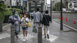 Pejalan kaki melintasi trotoar di kawasan Sudirman, Jakarta, Rabu (16/12/2020). Satgas Penanganan Covid-19 DKI Jakarta tengah membahas tentang kurva Covid-19 di wilayah Ibu Kota sembari mengkaji kebijakan WFH sebesar 75 persen bagi karyawan swasta. (Liputan6.com/Faizal Fanani)