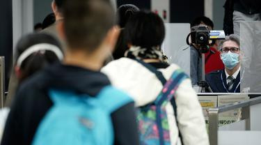 Petugas karantina (kanan) memantau para pelancong dari Wuhan China dan kota-kota lain ketika melewati pemindai suhu tubuh di Bandara Internasional Narita, Narita, Tokyo, Kamis (23/1/2020). Jepang meningkatkan pengamanan untuk mewaspadai penyebaran virus corona asal China. (AP Photo/Eugene Hoshiko)