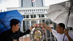 Massa saat menggelar aksi damai di depan Mahkamah Agung, Jakarta, Rabu (7/6). Dalam aksinya mereka menaburkan bungan pada payung sebagai bentuk simbol kekhawatiran matinya keadilan dan penegakan hukum. (Liputan6.com/Faizal Fanani)
