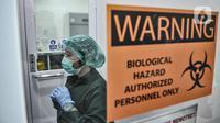 Tim medis mengenakan APD di ruang ganti sebelum memasuki laboratorium pemeriksaan Covid-19 di Labkesda DKI Jakarta, Selasa (4/8/2020). Labkesda DKI yang berjejaring dengan 47 lab se-Jakarta dalam sehari tercatat mampu menguji hampir 10.000 spesimen Covid-19 dengan metode PCR. (merdeka.com/Iqbal Nugr