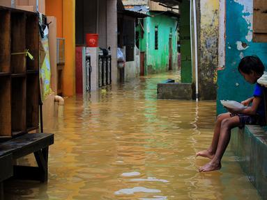 Seorang anak menikmati makanan saat banjir di kawasan Bidara Cina, Kecamatan Jatinegara, Jakarta Timur, Selasa (25/2/2020). Baru satu hari air surut, kawasan Bidara Cina yang bersebelahan dengan Kali Ciliwung kembali mengalami banjir. (merdeka.com/magang/ Muhammad Fayyadh)