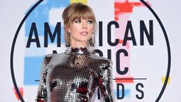 """Penyanyi Taylor Swift menghadiri ajang American Music Awards 2018 di Los Angeles, Selasa (9/10). Taylor Swift yang akan menampilkan lagu """"I Did Something Bad"""" datang dengan busana mirip bola disko yang menyilaukan mata (Kevork Djansezian/Getty Images/AFP)"""