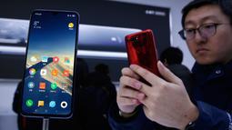 Seorang tamu undangan mencoba smartphone Xiaomi Mi 9 saat peluncuran di Beijing, China, Rabu (20/2). Sesuai rumor yang beredar, Mi 9 merupakan salah satu smartphone pertama yang resmi menggunakan Snapdragon 855. (AP Photo/Andy Wong)