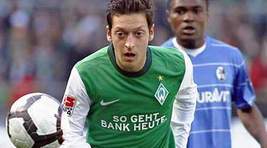 Aksi gelandang Werder Bremen Mesut Oezil (depan) dibayangi striker Freiburg Cedric Makiadi di laga lanjutan Bundesliga yang berlangsung di Bremen, 10 April 2010. Werder unggul 4-0. AFP PHOTO DDP / PHILIPP GUELLAND