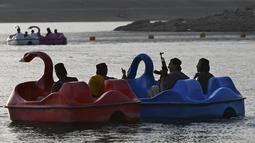 Sejumlah pasukan Taliban saat menaiki perahu kayuh di Danau Qargha di sebuah pekan raya di Kabul barat (28/9/2021). Mereka mengaku datang ke danau ini untuk bersenang-senang. (AFP/Wakil Kohsar)