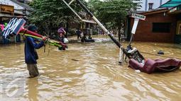 Seorang pedagang membawa dagangannya melewati banjir di kompleks Pondok Gede Permai, Jatiasih, Bekasi, Jumat (22/4). Pedagang berjualan alat kebersihan untuk membersihkan sisa lumpur yang terbawa banjir di kawasan tersebut. (Liputan6.com/Fery Pradolo)