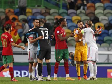 Para pemain berpelukan usai pertandingan persahabatan internasional antara Portugal dan Spanyol di stadion Jose Alvalade di Lisbon, Rabu (7/10/2020). Spanyol bermain imbang 0-0 atas Portugal. (AP Photo/Armando Franca)
