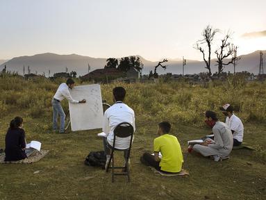 Para siswa mengikuti kelas luar ruangan di Kota Srinagar, Kashmir, India, Senin (6/7/2020). Kelas dimulai saat matahari terbit di tempat terbuka sesuai dengan aturan pencegahan jaga jarak sosial untuk melawan COVID-19. (Xinhua/Javed Dar)
