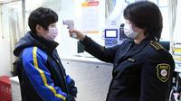 Seorang operator (kanan) mengukur suhu tubuh karyawan di sebuah terminal bus di Beijing, ibu kota China, pada 3 Februari 2020. Senin (3/2) menandai hari pertama masuk kerja setelah libur Tahun Baru Imlek di Beijing di tengah wabah virus corona. (Xinhua/Ren Chao)