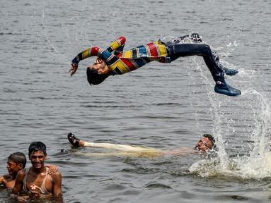 Pria dan anak muda Pakistan mendinginkan diri ke perairan Laut Arab saat musim panas di Karachi pada 5 Juli 2020. Mereka menghabiskan hari yang cerah dengan berenang di tengah pandemi virus corona. (Photo by Rizwan TABASSUM / AFP)