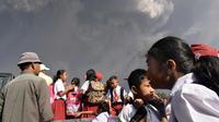 Anak-anak menaiki mobil saat terjadi erupsi Gunung Sinabung di sekolah dasar Sipandak di desa Tiga Pancur di Karo, Sumatra Utara (19/2). Gunung Sinabung aktif kembali tahun 2010 untuk pertama kalinya dalam 400 tahun terakhir. (AFP Photo/Anto Sembiring)