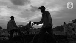 Petugas menyiapkan lahan makam jenazah dengan protokol COVID-19 di TPU Bambu Apus, Jakarta, Kamis (28/1/2021). Kamis (28/1), angka kasus kematian akibat terpapar COVID-19 di Indonesia mencatat rekor baru dengan jumlah 476 jiwa setelah hari sebelumnya 387 orang. (Liputan6.com/Helmi Fithriansyah)