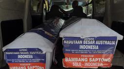 Petugas Kantor Pos mengirimkan dua peti mati ke kantor Kedutaan Besar Australia untuk Indonesia di Rasuna Said, Jakarta, Senin (9/3/2015).  Tampak, dua peti mati kiriman Bambang Saptono saat masih berada di dalam mobil. (Liputan6.com/Andrian M Tunay)