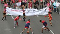 Para atlet yang mendukung penyelenggaraan Asian Games memeriahkan parade di Jalan MH Thamrin, Jakarta, Minggu (15/5). Total ada 42 rombongan dari berbagai komunitas, serta BUMN dan BUMS. (Liputan6.com/Arya Manggala)