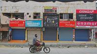 Pengendara motor melintas di depan pertokoan yang tutup di area komersial saat lockdown di Bangalore, Rabu (15/7/2020). Pusat IT India, Bangalore, kembali memberlakukan lockdown selama seminggu dimulai dari 14 Juli 2020 untuk menahan lonjakan kasus Covid-19 yang meningkat. (Manjunath Kiran/AFP)