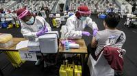 Vaksinator menyuntikkan vaksin COVID-19 dosis pertama produksi Sinovac kepada tenaga kesehatan saat vaksinasi massal di Istora Senayan, Jakarta, Kamis (4/2/2021). Kegiatan yang digelar Kemenkes dan Pemprov DKI Jakarta tersebut sebagai upaya percepatan vaksinasi COVID-19. (Liputan6.com/Johan Tallo)