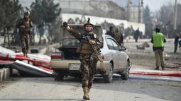 Petugas berjaga di lokasi serangan bom mobil bunuh diri di Kabul, Afghanistan (2/3). Menurut Kemendagri Afganistan, Najib Danish, menyebutkan, ledakan terjadi di dekat sebuah kendaraan milik pekerja asing di sebelah timur kota. (AFP Photo/Wakil Kohsar)