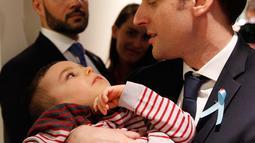 Presiden Prancis Emmanuel Macron menggendong seorang anak saat mengunjungi Graffiti's- Association Le Moulin Vert di Normandia, Prancis (5/4). Pada kunjungannya Presiden Emmanuel Macron berinteraksi dengan anak-anak autis.  (AP / Christophe Ena, Pool)