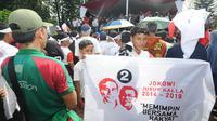 Seorang simpatisan terlihat membawa spanduk Jokowi-JK di lapangan Situ Buleud di Kabupaten Purwakarta, Jawa Barat, Selasa (17/6/14). (Liputan6.com/Herman Zakharia)