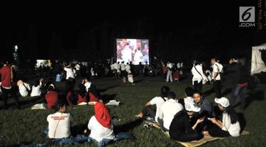 Para pendukung Capres dan Cawapres nomor urut 01 dan 02 saat nonton bareng Debat Perdana Pilpres di kawasan Gedung Bidakara, Jakarta, Kamis (17/1). Mereka menonton dengan layar tancap yang disediakan warga sekitar. (merdeka.com/Iqbal S Nugroho)