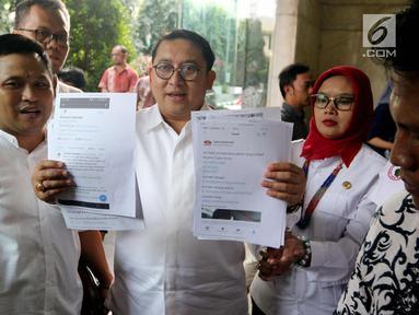 Sekjen Partai Gerindra Fadli Zon menunjukkan berkas laporan penyebar berita hoax kepada Ketum Partai Gerindra Prabowo Subianto saat mendatangi gedung Bareskrim Mabes Polri, Jakarta, Jumat (2/3). (Liputan6.com/Johan Tallo)