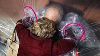 Diane Rossi (Kiri) memeluk suaminya, Arthur Rossi, melalui tenda pelukan di komunitas Crossroads Senior Living di Lakewood, Colorado, Jumat (26/2/2021). (Michael Ciaglo/Getty Images/AFP)