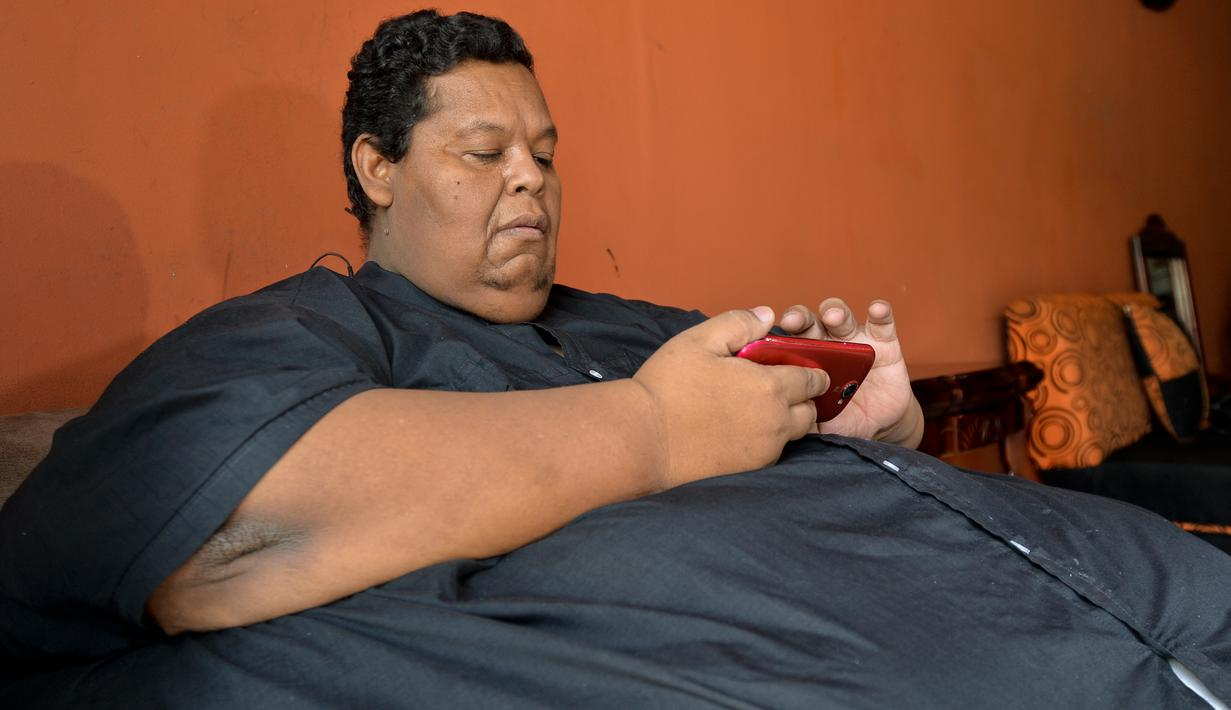 Oscar Vasquez Morales (44) memeriksa ponselnya di Palmira, Kolombia, 19 Maret 2016. Setelah selama berpuluh tahun mengonsumsi junk food, berat badan Oscar melonjak hingga 400 kilogram. (AFP PHOTO/Luis ROBAYO)
