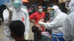 Petugas medis melakukan swab tes Covid-19 pemilik kios di pasar Perumnas Klender, Jakarta, Jumat (29/5/2020). Sebanyak, 50 pedagang pasar menjalani Rapid Test dan Swab Test untuk kedua kalinya yang mana sudah dilakukan sebelumnya ada hasil reaktif lima orang pedagang pasar. (merdeka.com/Imam Buhori)