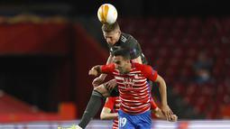 Gelandang Manchester United, Scott McTominay berebut bola dengan pemain Granada, Angel Montoro pada pertandingan leg pertama perempat final Liga Europa di stadion Los Carmenes di Granada, Spanyol, Jumat (9/4/2021). MU menang atas Granada 2-0. (AP Photo/Fermin Rodriguez)