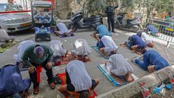 Anggota pasukan keamanan Israel berjaga saat seorang jemaah Palestina melaksanakan salat Jumat selama bulan suci Ramadan di tengah krisis pandemi coronavirus di luar kompleks masjid al-Aqsa di Kota Tua Yerusalem (15/5/2020). (AFP/Ahmad Gharabli)